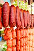 Home made meat salami sausage at street market hanging in line under sunlight Stock Photos