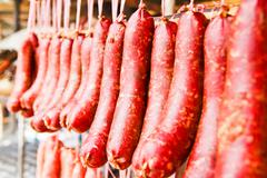 home made meat salami sausage at street market hanging in line under sunlight - stock photo