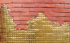 Golden mosaic on red brick wall Stock Photos