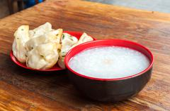 A typical Chinese breakfast of congee and fried pork dumplings Stock Photos