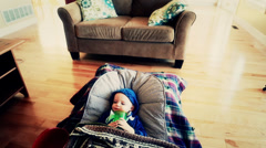 A toddler with the flu lying on the floor jib shot Stock Footage