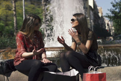 Two girlfriends arguing by the fountain, super slow motion, shot at 240fps NTSC Stock Footage