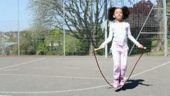 Young child using a jump rope to skip backwards outdoors on a sunny day Stock Footage