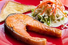 salmon steak with salad and bread - stock photo
