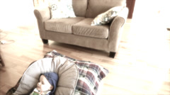 A toddler with a flu lying on a floor jib shot Stock Footage