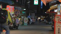 Evening - 2 men bike through town of ita thao Stock Footage