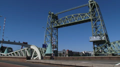 Railway lift bridge De Hef or Koningshavenbrug in Rotterdam + pan city traffic Stock Footage