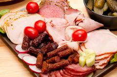 platter of cold cuts and sausages with ham and tomatoes - stock photo
