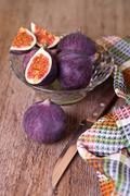 fresh figs, old knife and chequered towel - stock photo