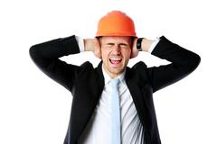 Stock Photo of businessman in helmet covering his ears over white background