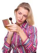 Woman applying make-up - stock photo