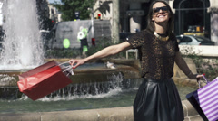 Happy woman with shopping bags by the fountain in the city HD Stock Footage