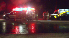 Accident scene at night with victim and ambulance Stock Footage