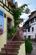 street with half-timbered medieval houses in eguisheim village - stock photo