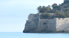 Palm trees on garden of fortress walls of castle by the sea Stock Footage