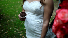 Pregnant bride holding muffin and standing next to her future husband Stock Footage