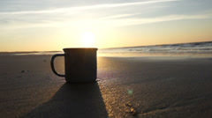Pouring tea or coffee from thermos with sunset at the beach Stock Footage