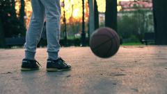 Teenager bouncing basketball ball on court during sunset HD Stock Footage