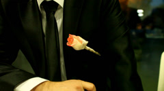 Sitting bridegroom wearing rose on his tux waiting on bride Stock Footage