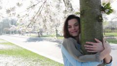 Woman hugging blossom tree with tilt up and down Stock Footage