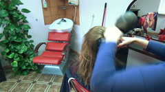 Professional barber dry client girl hair haircut in salon Stock Footage