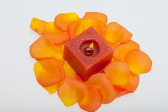 spilt petals of the orange-rose around the aromatic candle - stock photo
