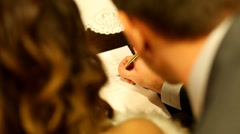 Groom signing wedding document - stock footage
