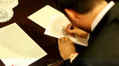 Groom signing wedding document Stock Footage