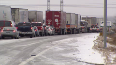 Trucks and tractor trailers stuck on icy highway - stock footage