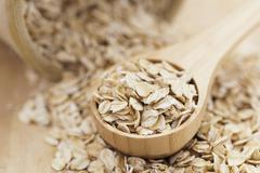 Healthy dry oatmeal in a wooden spoon Stock Photos