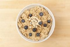 organic cooked oatmeal with blueberries - stock photo