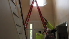 Construction worker descends from ladder in interior house foyer Stock Footage