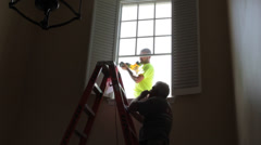 Men replace second story window Stock Footage