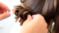 Hair stylist curling hair of future married woman Stock Footage
