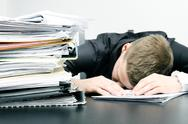 Stock Photo of tired office worker and a pile of documents