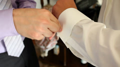 Two mens attaching cuff links a moment before wedding Stock Footage