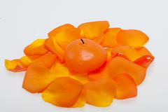 Spilt petals of the orange-rose around the aromatic candle Stock Photos