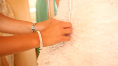Brides maid helping bride getting dressed Stock Footage