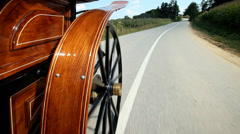 Horse drawn carriage wheel spinning on road Stock Footage