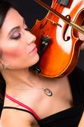 sensual attractive brunette woman playing concert acoustic stringed violin - stock photo