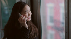 Young Asian woman talking on cellphone on subway train Stock Footage