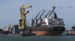 Bulk handling + zoom out - reload dry bulk from seagoing ship to barge Stock Footage