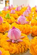 Row of lotus and yellow flower garlands on tray with pedestal in thai temple, Stock Photos