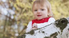 Vauva suosionosoitukset. Pikkutyttö istuu koivun, kiittää Arkistovideo
