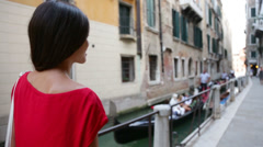 Venice, Italy - woman in dress walking by canal Stock Footage