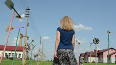 Girl with skirt go between spin toy pinwheel windmills avenue Stock Footage