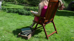 Girl in shorts sit on wooden chair and read study book Stock Footage