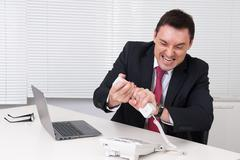 Angry business man screaming at phone in his office Stock Photos