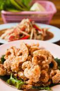 Crispy pork salted rind with thai herbal and papaya salad on the table Stock Photos