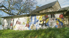 Slow dolly into graffiti on rural building Stock Footage